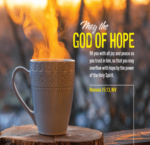 "A steaming coffee cup rests on a porch rail at a log cabin. Text is Romans 15:13--""May the God of hope fill you with all joy and peace as you trust in him, so that you may overflow with hope by the power of the Holy Spirit."""