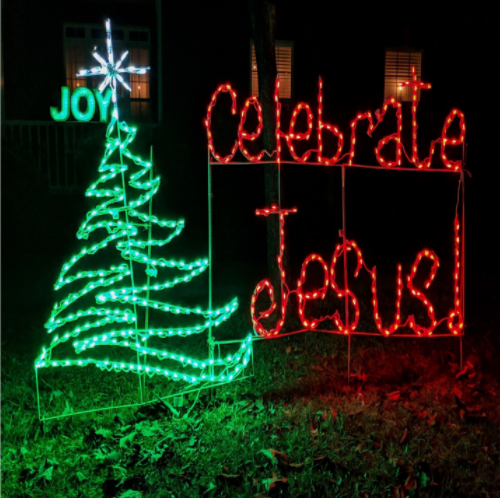 """An illuminated Christmas tree is on a lawn. Next to it in bright red lights we see the words, """"Celebrate Jesus!"""""""